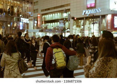 TOKYO - NOVEMBER 30, 2017: Rear view of a young Japanese couple crossing the crowded Shibuya Crossing. The Shibuya Crossing is rumoured to be the busiest intersection in the world.