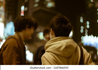 TOKYO - NOVEMBER 30, 2017: Rear view of three young male friends standing and chatting by the famous Shibuya Crossing. The Shibuya Crossing is rumoured to be the busiest intersection in the world.