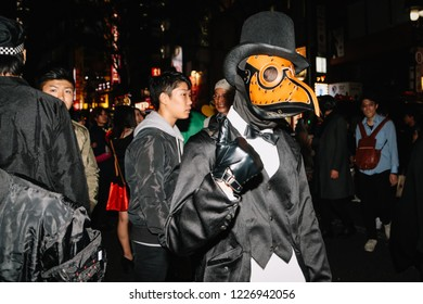 TOKYO - OCTOBER 31, 2018: A man wears a plague mask at the Shibuya Halloween street party in Tokyo, Japan on the night of October 31, 2018.