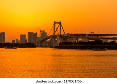 Tokyo skyline and rainbow bridge at sunset in Odaiba waterfront