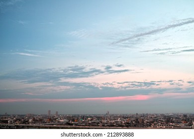 Tokyo skyline under blue sky with flowing clouds