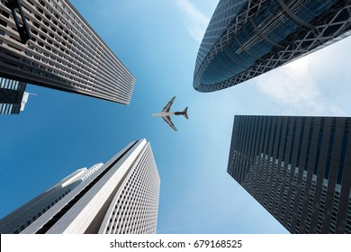 Tokyo skyscrapers buildings and a plane flying overhead at in Tokyo Shinjuku downtown and business district in morning at Tokyo, Japan.