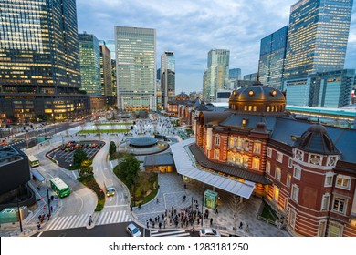 Tokyo Station, Tokyo, Japan - December 26, 2018: Railway or train station in Marunouchi surround by cityscape of business district of Chiyoda, twilight time in the evening.