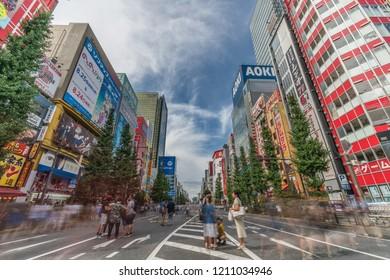 Tokyo, Taito Ward, Akihabara - August 19, 2018 : Motion blurred people walking along shops and Colorful Billboard Advertisements at famous Akihabara Electric Town