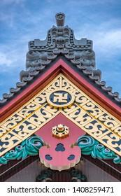 Tokyo, Taito Ward - August 18, 2018 : Onigawara ogre goblin tile roof ridge detail, Crooked cross and Kazarikanagu Metal ornaments roof ridge deatil at Senso-ji temple