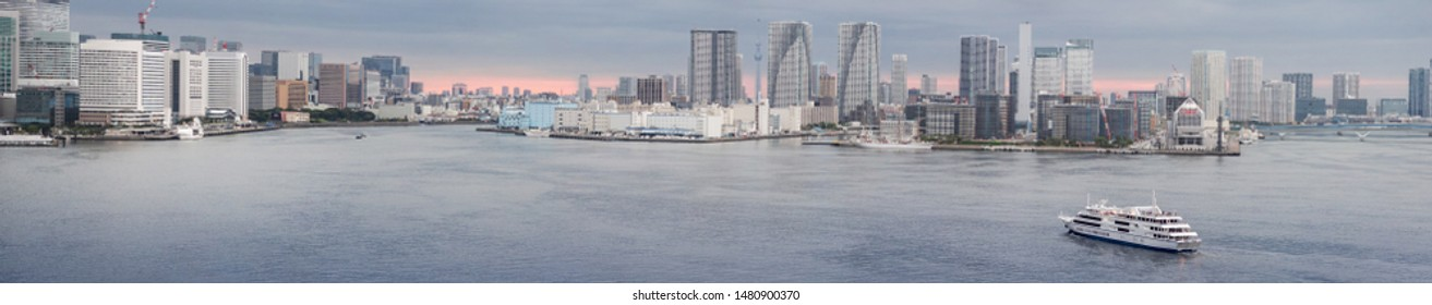 Tokyo tourist seaport with the piers of Takeshiba on the left, of Tsukishima in the center and the Harumi passenger terminal on the right at twilight.