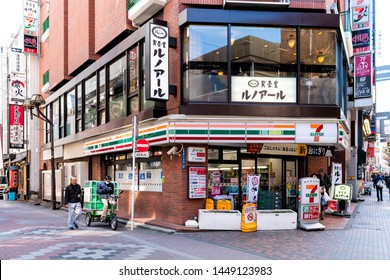 Tokyo, USA - April 4, 2019: Shinjuku city district ward with 7-eleven or Seven Eleven convenience store shop storefront or facade with people walking
