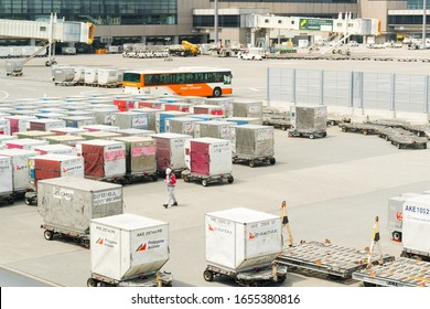 Tokyo/Japan - August 26, 2019: Aircraft ground crew walking in loading area full of unit load devices (ULD) and flatbed dollies for inspection before transfer baggages to airplane in Nariata airport.