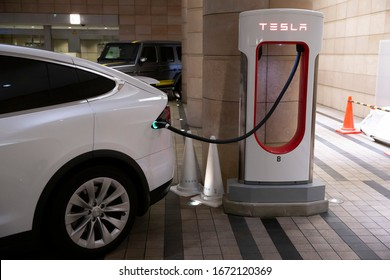 Tokyo/Japan February 25, 2020  Tesla plug-in electric car Model X been charged by a Supercharger network in Supercharger station.