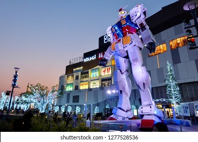 Tokyo/Japan -july 2016: previous famous big powerful MOBILE SUIT GUNDAM in front of Odaiba Divercity Tokyo Plaza with evening night beautiful purple pink sunset glow cloud. shining illumination around