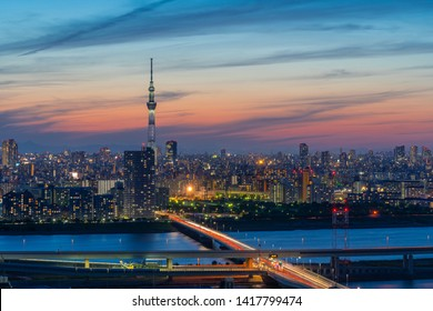 TOKYO/JAPAN - MAY 8 2019: Tokyo Skyscraper Cityscape under VivId and Colorful Sunset Twilight Sky with Tokyo Skytree, Buildings, Road with Traffic Light, and Sumida River.