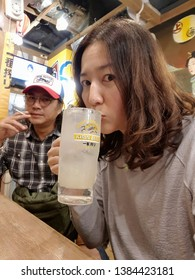 Tokyo,Japan-Circa September 2017: Woman sits with a smoking man and holds a glass of Japanese highball beverage to enjoy sipping in the vibrant ambiance of local restaurant.