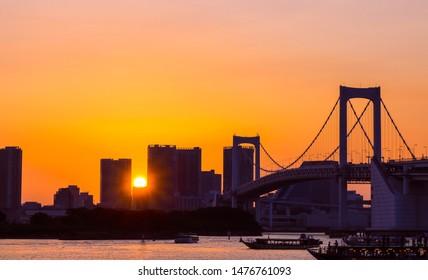 Tokyo/Japan-July 30 2019:Dramatic shot of Tokyo Rainbow bridge taken during a fiery sunset at Odaiba City.