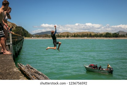 TOLAGA BAY WHARF, NEW ZEALAND - CIRCA JANUARY 2018 young people diving and jumping off the longest wharf in the Southern Hemisphere, a popular summer activity for locals and tourists alike.