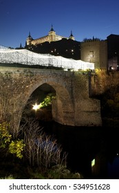Toledo illuminated, Spain, Lighting of the Christmas holidays on the bridge of Alcántara, of Roman and Arab origin, also illuminated the military building of the Alcázar of Toledo,