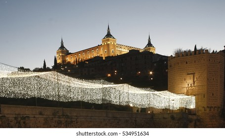 Toledo night illuminated, Spain, Lighting of the Christmas holidays on the bridge of Alcántara, of Roman and Arab origin, also illuminated the military building of the Alcázar of Toledo,