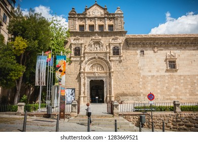 Toledo, Spain - April 28, 2018: Woman walking in front of the Santa Cruz Museum in Toledo on a spring day. Plateresque building of the sixteenth century