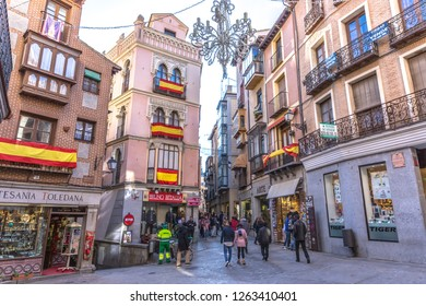 Toledo, Spain - Dec 5th 2017 - Tourists and locals walking in the narrows streets of Toledo with restaurants and plenty of Spain flags