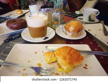 TOLEDO, SPAIN - MARCH 26, 2018: puff pastry with custard, muffin, donut, cappuccino and tea on the table in the popular Toledo cafe.