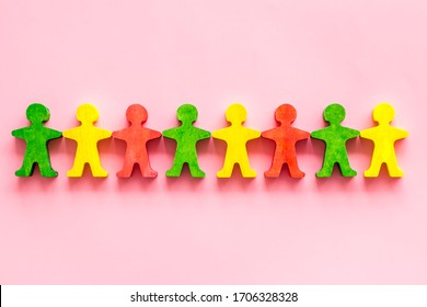 Tolerance, social protection, anti-discrimination concept. Wooden human figures on pink table, top view
