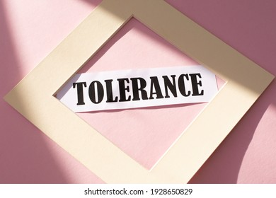 tolerance text in a beige frame on a pink background.Equality, diversity and tolerance concept.