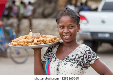 Toliara, Madagascar - January 10th, 2019: A local malagasy woman selling Nem - eggrolls in the streets at the market in Toliara, Madagascar.