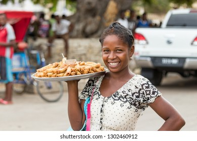 Toliara, Madagascar - January 10th, 2019: A local young malagasy woman selling Nem - eggrolls, smiling, in the streets at the market in Toliara, Madagascar.