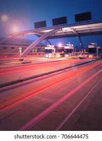 Toll booth with streaming lights and signs at night