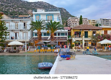 Tolo, Greece – July 09, 2013: Hotels on the beach of Mediterranean Sea with people and mountains on the background