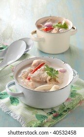tom kha gai or coconut milk soup with chicken breast. The populat Thai menu, ready to serve in a white pot.