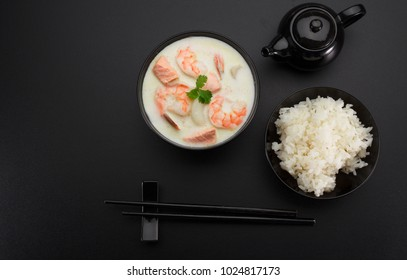 Tom kha soup with seafoods over dark background.