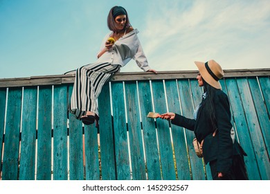 Tom Sawyer Pretty woman in the straw hat standing in front of fence. The woman painted a wooden fence.