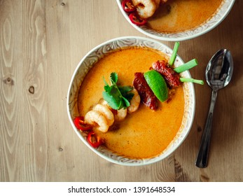 Tom yam kong ready-to-eat. Tom yum soup with shrimps on wooden table. Popular spicy Thai dish Tom Yam top view. Thailand food and Thai cuisine. Copy space for text. Natural day light