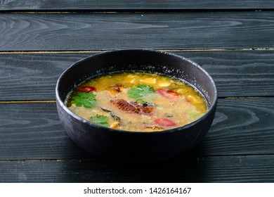 Tom yam kong or Tom yum, Tom yam is a spicy clear soup typical in Thailand, Thai Dish Cuisine. Tom yam kong on wooden table. Thai food.