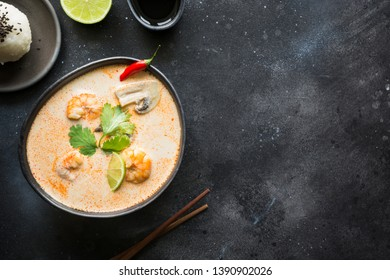 Tom yam kung spicy thai soup with shrimp, seafood, coconut milk, chili pepper and rice. View from above. Space for text.