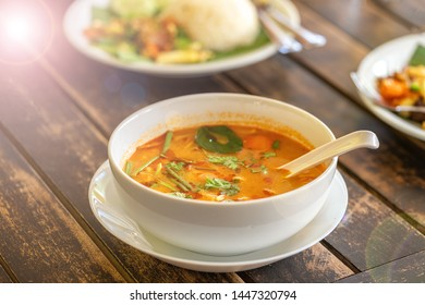 Tom Yam Kung, Thai cuisine. on a wooden table. Background - other Thai dishes