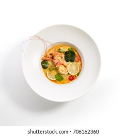 Tom yam kung - Thai soup with shrimp and coconut milk with slices of fruit and vegetables and fresh herbs in white plate. Pan-Asian menu in restaurant. Top View.