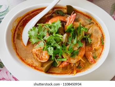 Tom yam kung, the traditional Thai sour soup with prawns, topped with coriander. The photo shows the red version of the soup, made with coconut milk, also called tom yam kathi. Shallow depth of field.