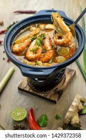 Tom Yam Kung or Tom Yum soup is Thai hot spicy soup shrimp or prawn with lemon grass, lemon, galangal, mushrooms, coconut milk and chilli in bowl on wooden table top view, famous Thai food cuisine.