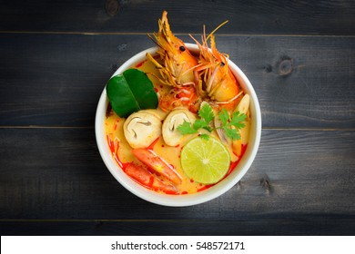 Tom Yum Goong Spicy Sour Soup on wooden table top view, Thai local food
