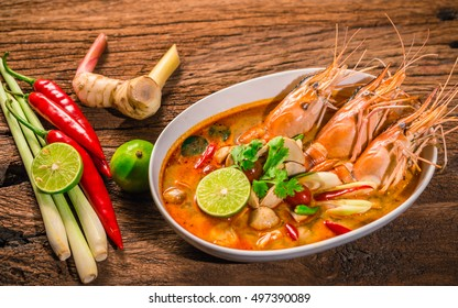 Tom Yum Goong Thai hot spicy soup shrimp  with lemon grass,lemon,galangal and chilli on wooden background Thailand Food
