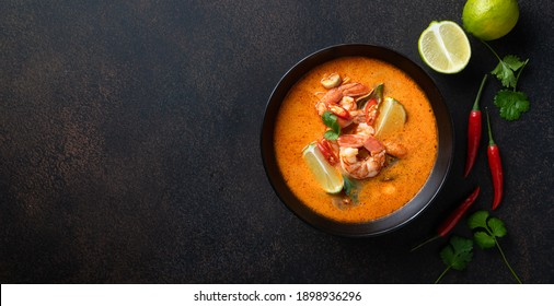tom yum kung Spicy Thai soup with shrimp in a black bowl on a dark stone background, top view, copy space