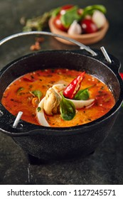Tom Yum or Tom Yam with Squid, Shrimp, Chili Peppers, Lime Juice, Galangal, Fish Sauce, Lemongrass. Hot and Sour Thai Soup Cooked with Fragrant Spices. Traditional Thailand Food on Dark Background