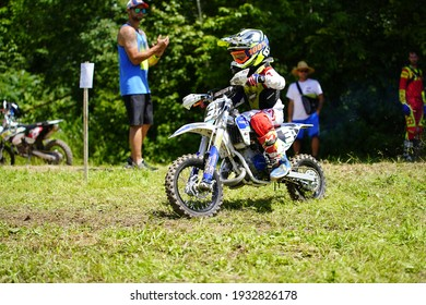 Tomah, Wisconsin USA - October 11th, 2020: Youth dirt bike riders travel through forest track in a motocross race event.