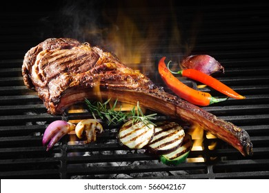 Tomahawk rib beef steak on hot black grill with flames