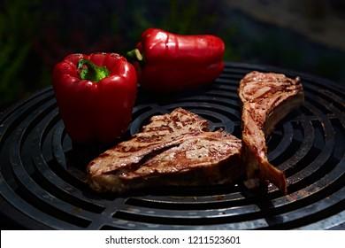 Tomahawk rib beef steak and T-bone on hot black grill.
