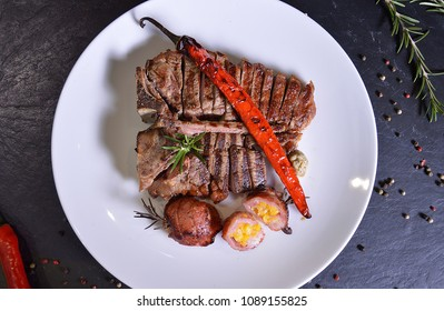 Tomahawk steak in marinade Jack Daniels and demiglas sauce with whiskey. Fresh grilled meat. Grilled beef steak medium  on  plate. Top view.