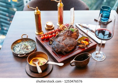 Tomahawk steak with mash potato, baked spinach cheese and gravy sauce. Served with red wine.