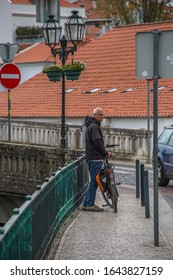 Tomar / Portugal - 04 04 2019 : View of a senior tourist man with his bike on downtown Tomar city, looking to other side at the street