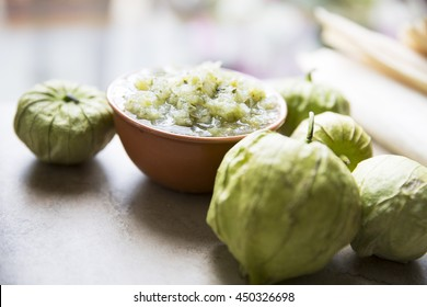 Tomatillos and  a bowl of green salsa on stone surface.